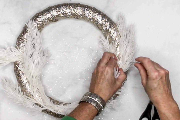 Evergreen being attached to a glittery wreath