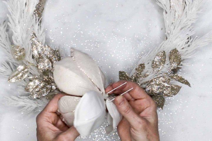 Flower being pinned to DIY foam wreath