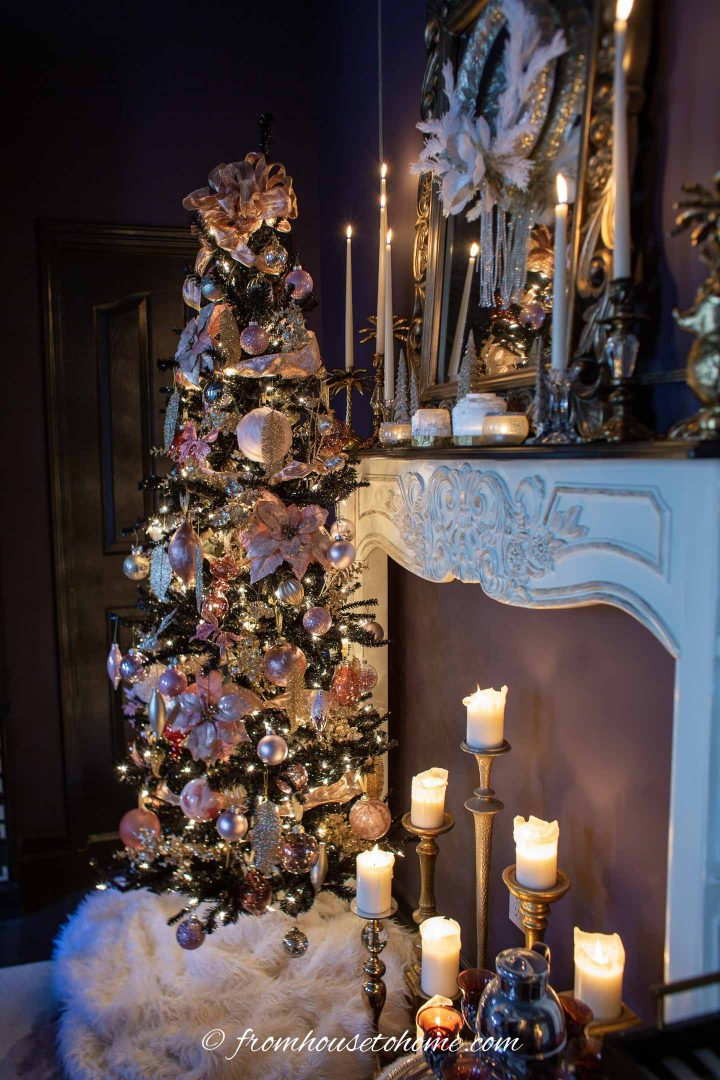 Pink and gold Christmas tree beside a fireplace mantel covered in candles
