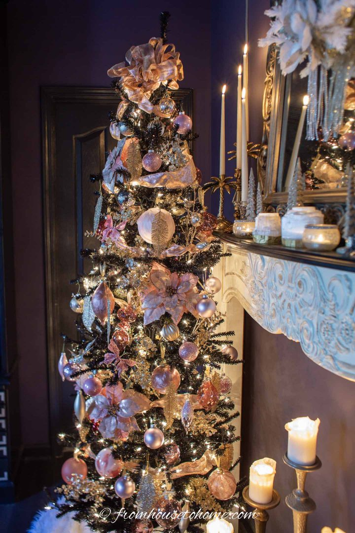 Black Christmas tree decorated with pink and gold ornaments beside a fireplace mantel