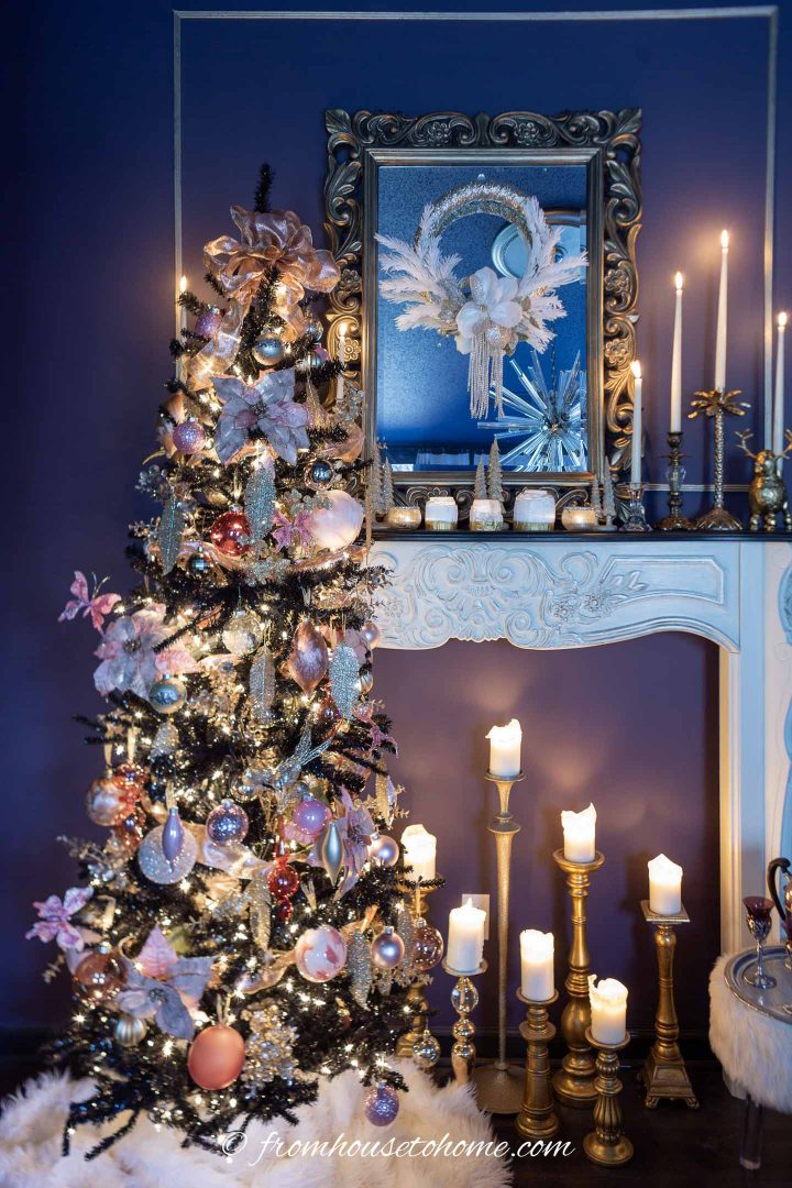 Christmas tree decorated in pink and gold beside a fireplace mantel with a mirror over it