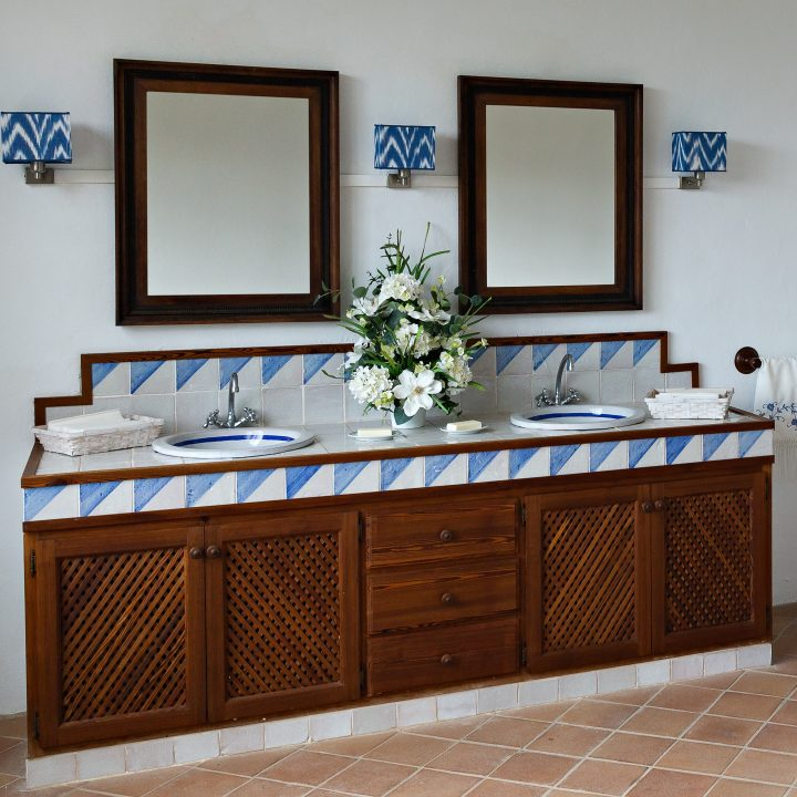 Spanishh style bathroom with wood cabinets and blue and white ties ©arbalest - stock.adobe.com