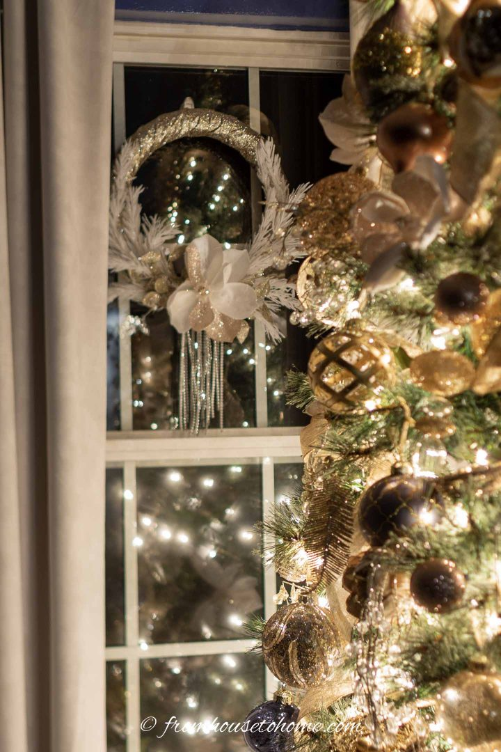 Gold and white wreath hung in the window behind the Christmas tree