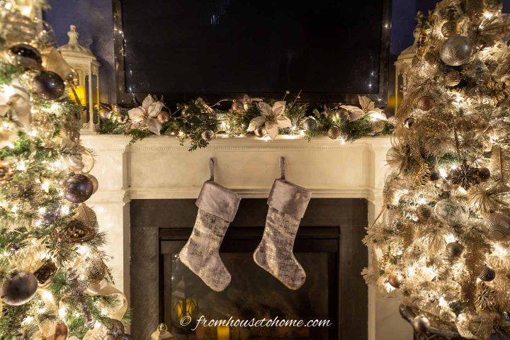 Fireplace mantel decorated for Christmas with stockings, a garland and 2 Christmas trees on either side
