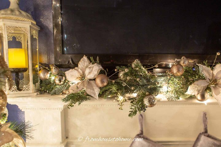 A Christmas garland on a mantel made with faux evergreens, white and gold poinsettias and copper and gold Christmas ornaments
