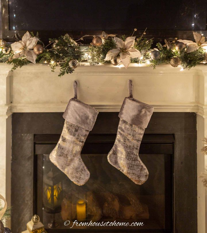 A fireplace mantel with a Christmas garland on top and 2 silver stockings hung on the front