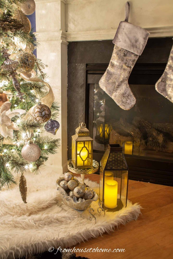 Two lanterns and a decorative sleigh filled with Christmas ornaments between the Christmas tree and the fireplace