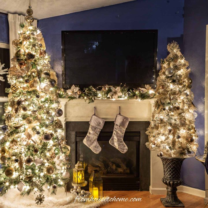 Two Christmas trees on either side of the fireplace, all decorate with gold, silver and copper ornaments