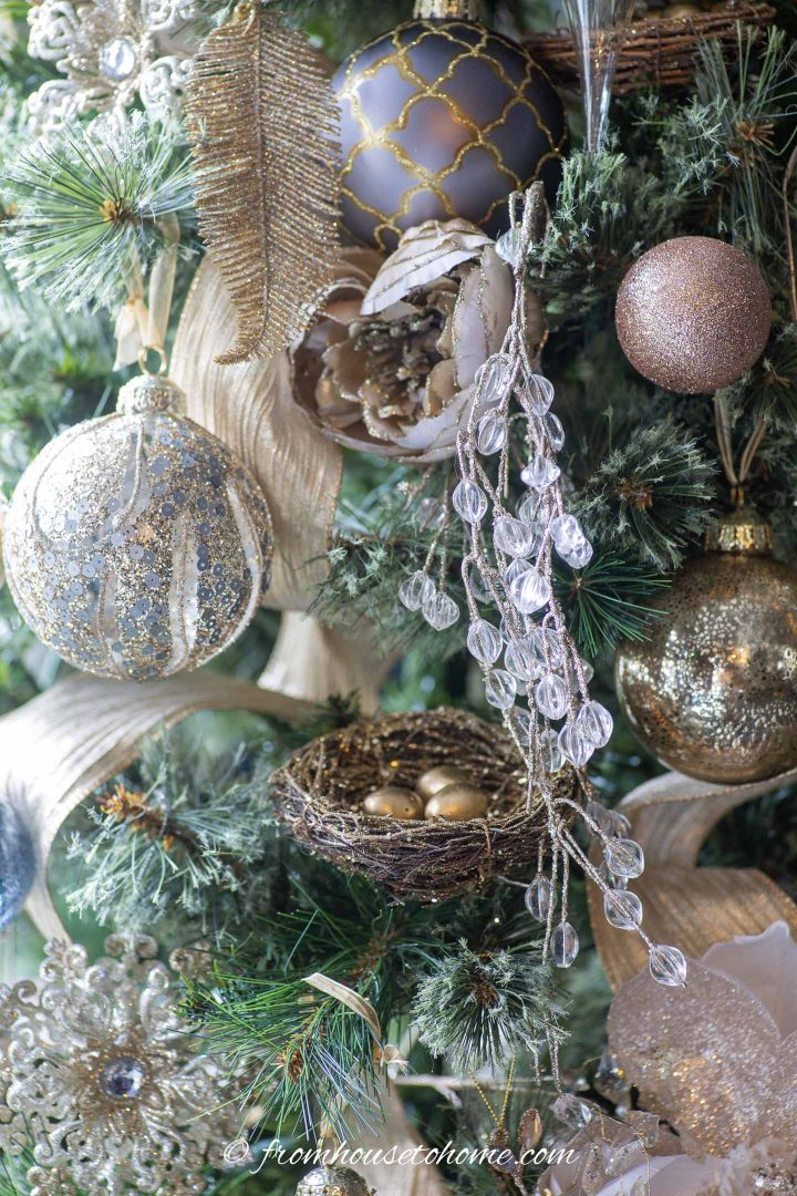 DIY bird's nest ornament on a Christmas tree with gold and silver ornaments