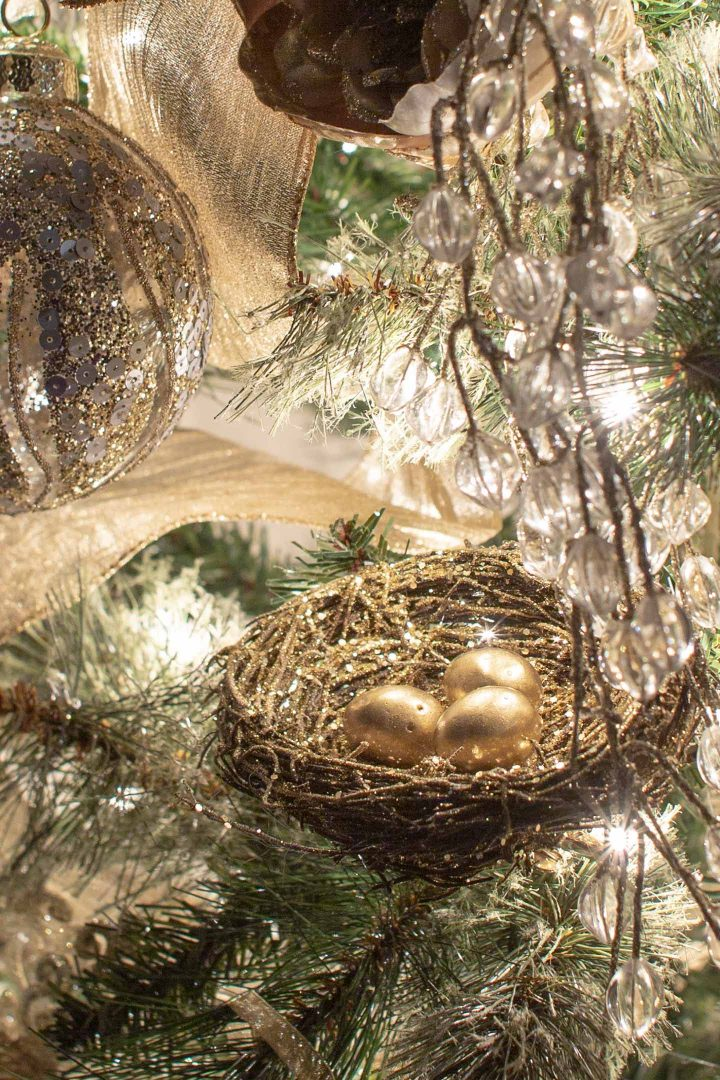 Gold DIY bird's nest ornament on a Christmas tree at night
