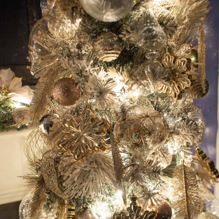 Copper, silver and gold ornaments on a flocked Christmas tree