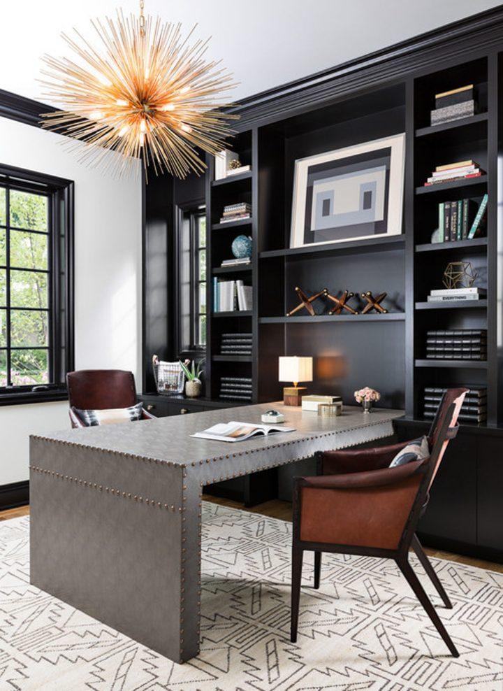 Silver desk perpendicular to black bookshelves