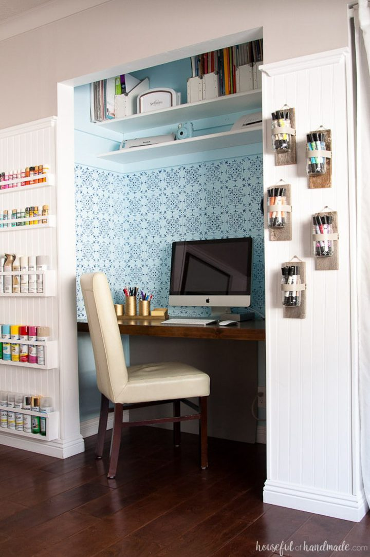 Closet home office with a blue stenciled pattern on the wall behind the desk