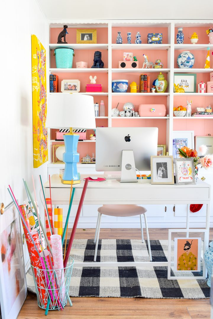 White home office desk in front of bookshelves that are painted pink