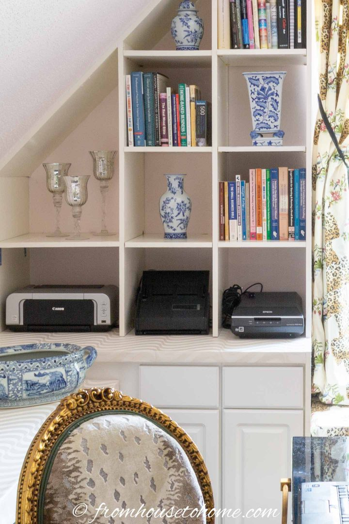 A printer and scanners stored in a home office shelf