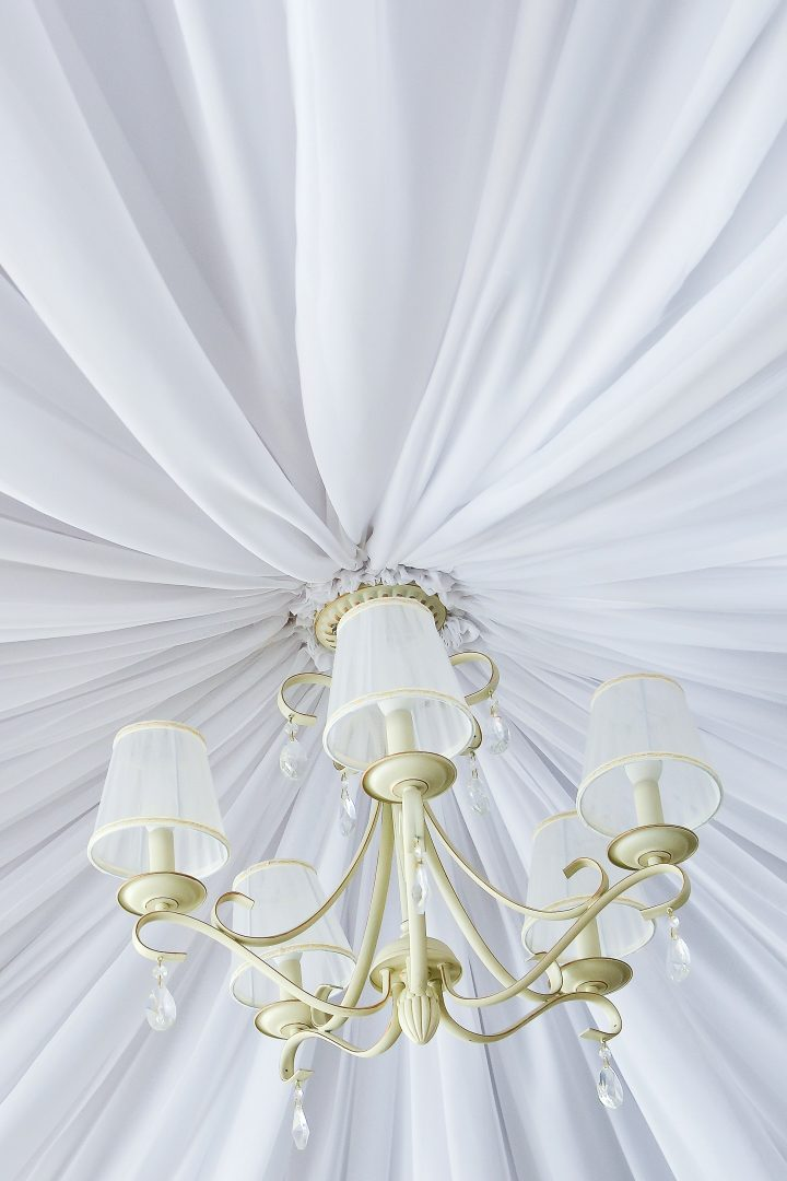 Fabric on the ceiling installed around a chandelier ©kyrychukvitaliy - stock.adobe.com