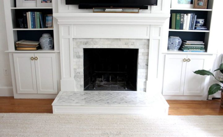 Bookcases on either side of a fireplace with doors added on the bottom by Lisa from shineyourlightblog.com