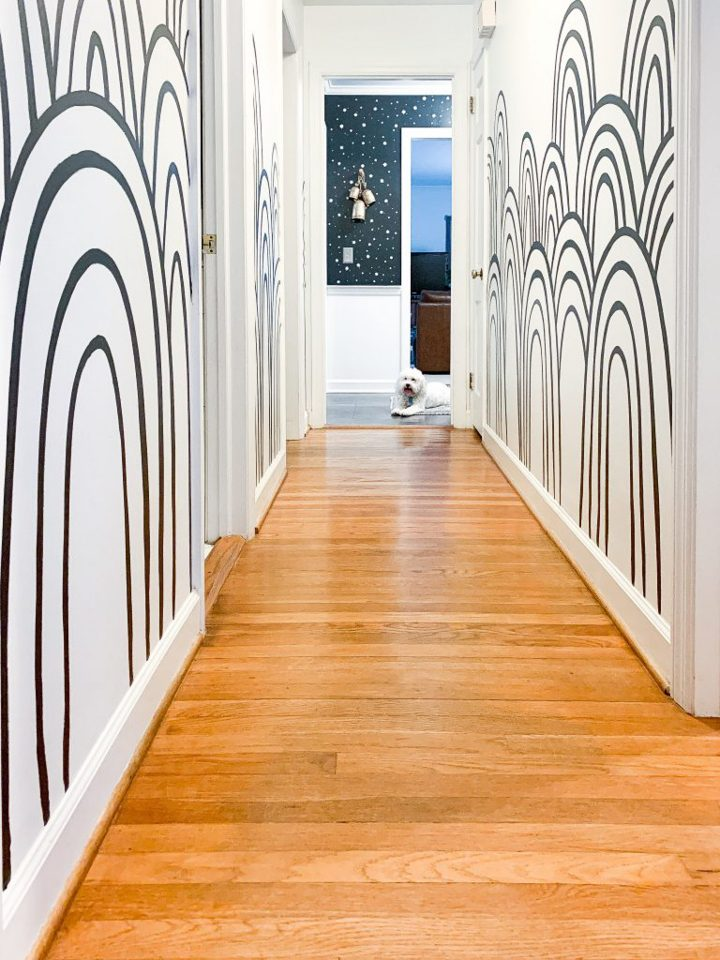 Hallway painted with black and white hills mural