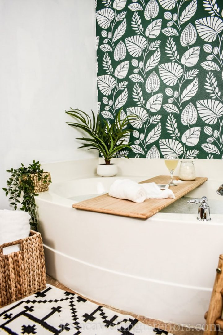 Wall behind a bathtub painted with a botanical leaf print stencil via jessicawellinginteriors.com
