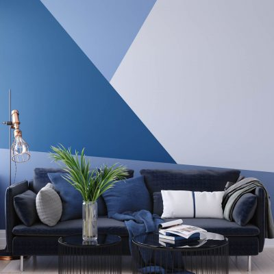 blue living room with triangle design painted on the wall behind the couch