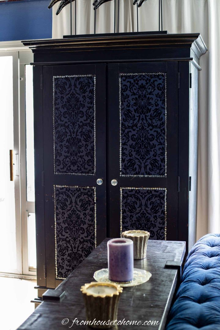 Armoire with upholstery tack detail on the front