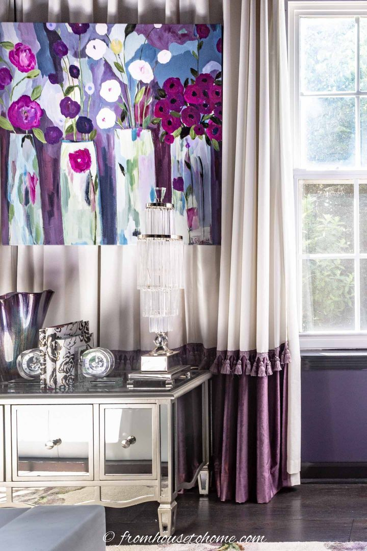 White and purple curtains with tassel trim behind a console table