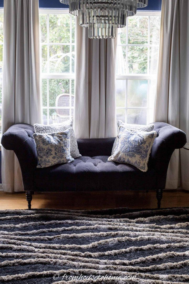 Black sofa with blue and white cushions on a black and gray area rug