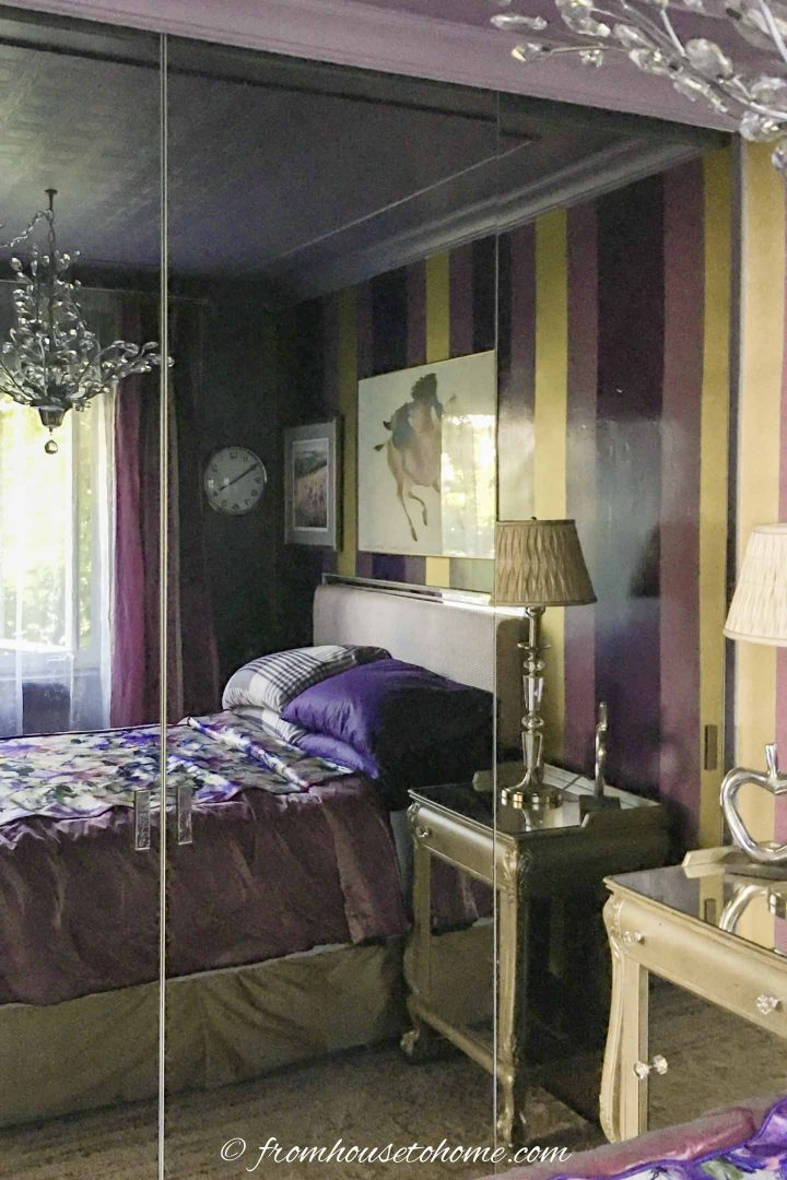 Bedroom with an accent wall behind the bed painted with vertical stripes