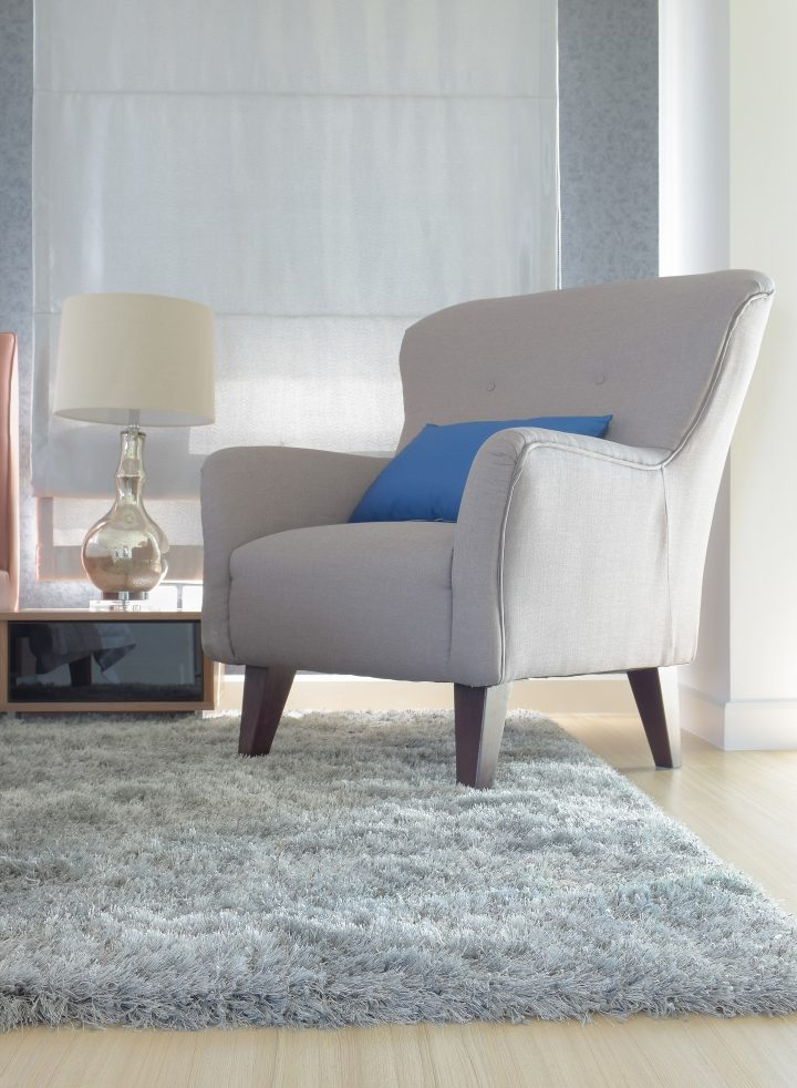 Upholstered chair with a cozy area rug under it