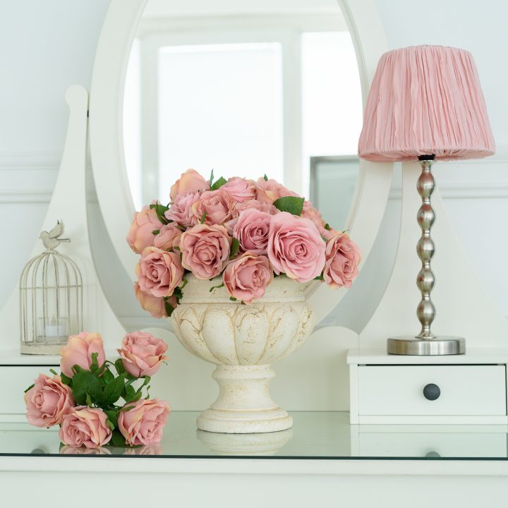 White dresser with pink roses and a pink lamp shade