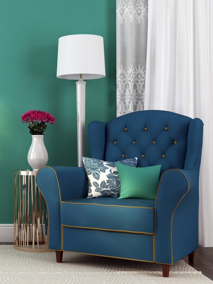 Blue arm chair in front of a teal wall