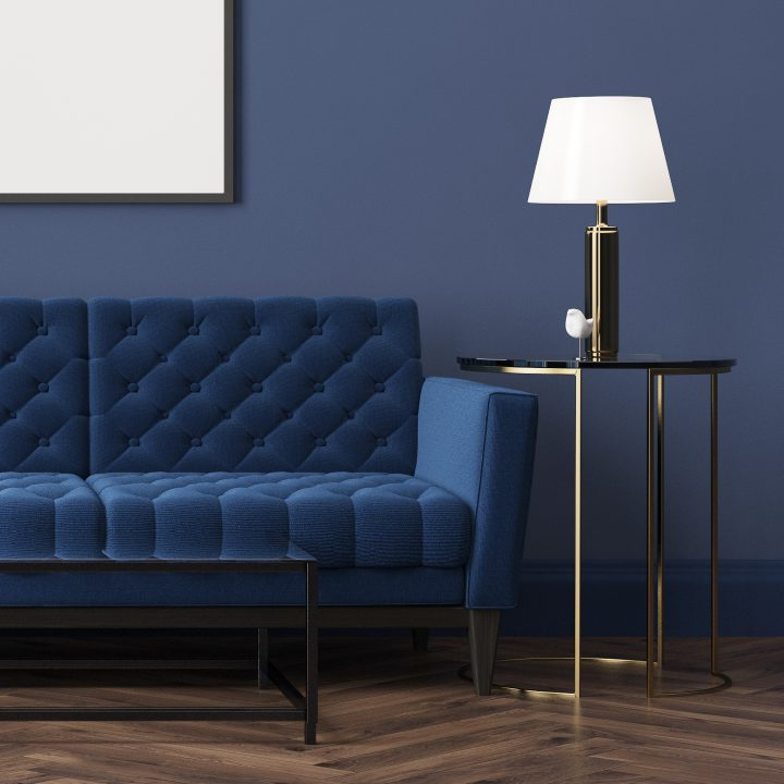 Cozy living room with blue velvet sofa and blue walls