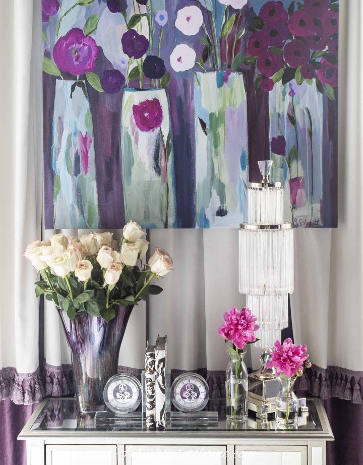Colorful picture hung above a table with a vase or flowers and other accessories