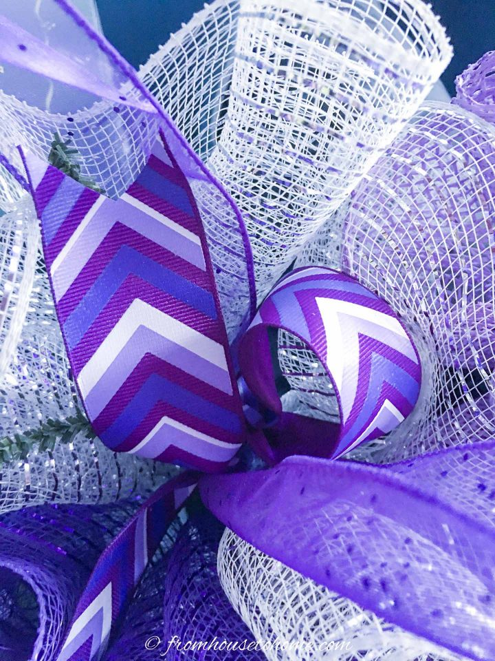 The ribbon attached to the deco mesh Christmas wreath