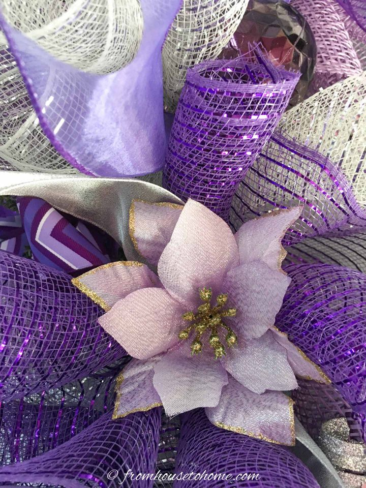 The mauve poinsettia ornament attached to the deco mesh Christmas wreath