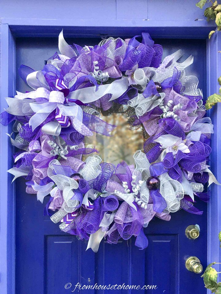 The finished DIY purple and silver deco mesh Christmas wreath hung on the door