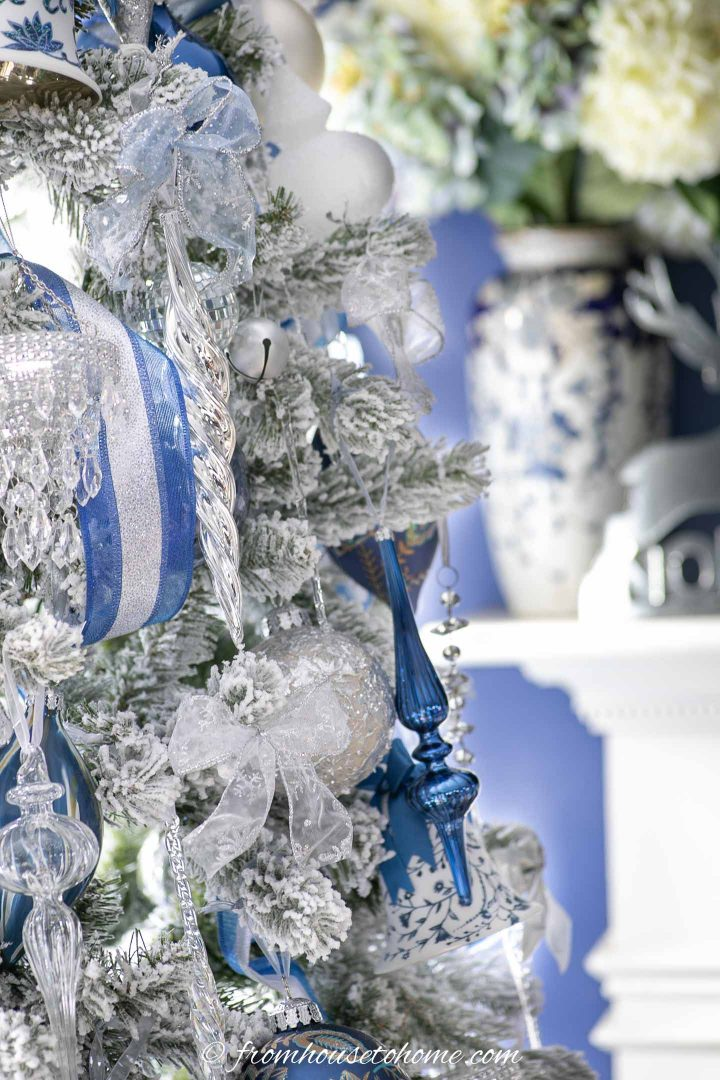 blue, white and clear glass finial ornaments on a flocked christmas tree