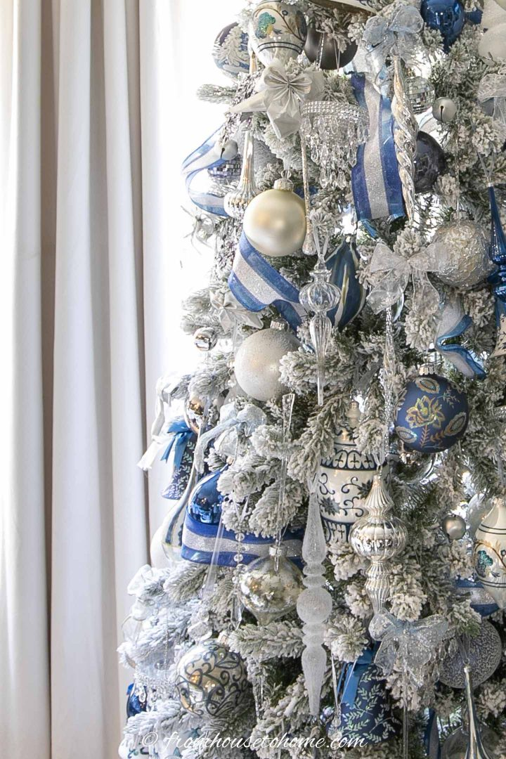 blue and white ribbon with blue, white and silver ornaments on a christmas tree