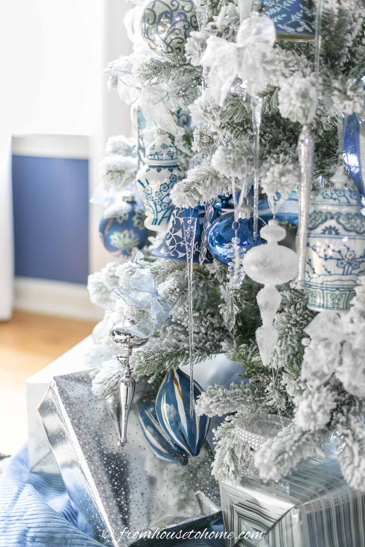 Christmas presents wrapped in silver wrapping paper under a wintry white, blue and silver christmas tree