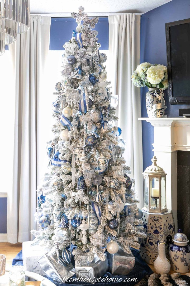 Wintry white, blue and silver Christmas tree in front of the window