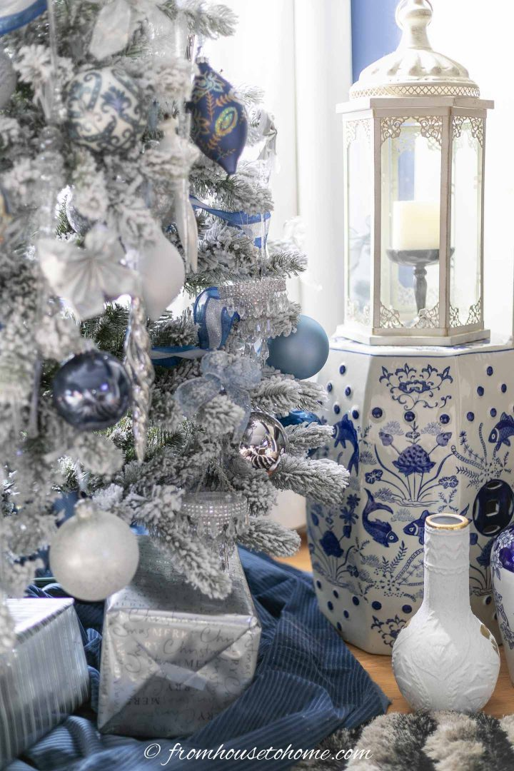 blue and white garden stool beside a wintry white, blue and silver christmas tree