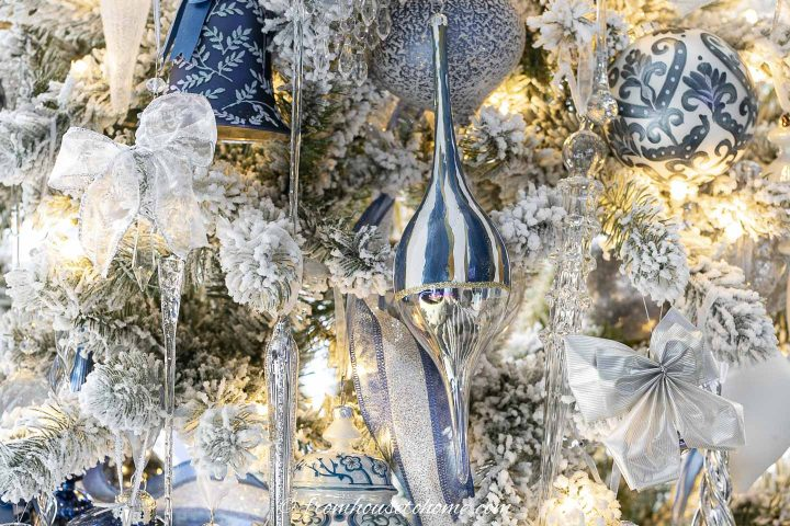 white lace and silver bows tied to the branches of a flocked christmas tree