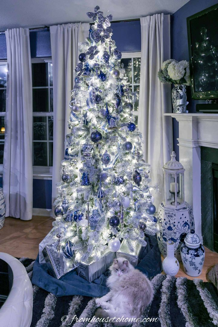 Wintry white, blue and silver christmas tree with the lights on at night