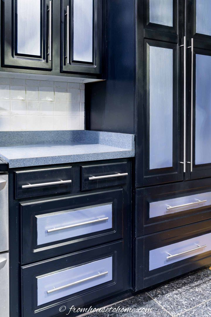 Black kitchen cabinets with silver accents