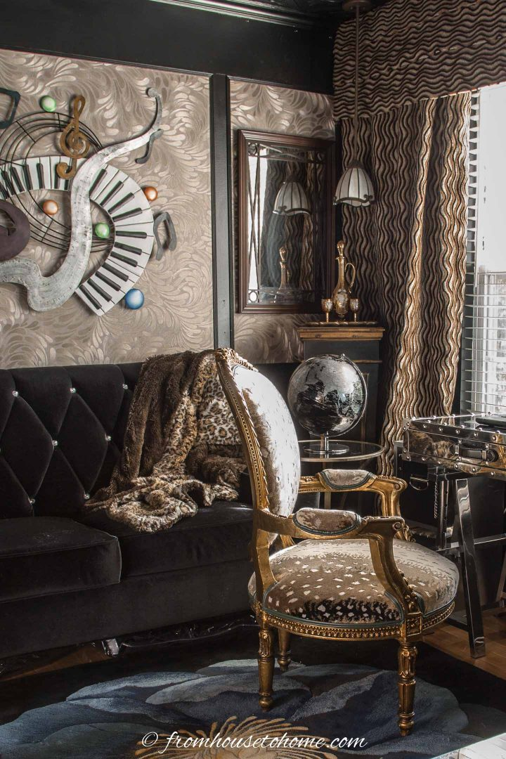 Black velvet sofa in a small black and gold home office