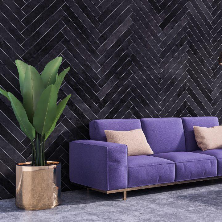 Black herringbone pattern on a wall behind a purple sofa