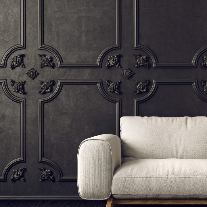 Black walls with panel moldings and a white sofa