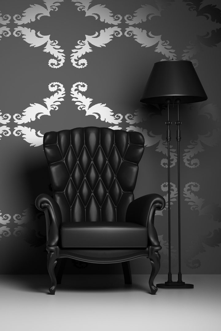 Black leather chair and lamp in a room with black and silver wallpaper
