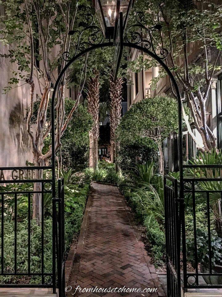 Wrought iron arbor over a path leading into a garden room