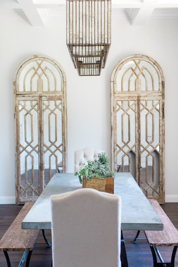 Simple dining room with two large arched mirrors at one end of the dining table